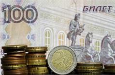 Монеты евро на фоне рублевой купюры в Зенице 21 апреля 2015 года. Рубль подешевел на торгах понедельника, невзирая на пик налогового периода, из-за ожиданий снижения ключевой ставки ЦБР в ближайший четверг, а также на фоне сужения активности экспортеров, которые могли заранее продать основные объемы валютной выручки под уплату ключевых налогов 27-28 апреля. REUTERS/Dado Ruvic