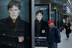 A man looks at posters of actor Robert Redford during the Chaplin award at Alice Tully Hall in New York April 27, 2015. REUTERS/Eduardo Munoz