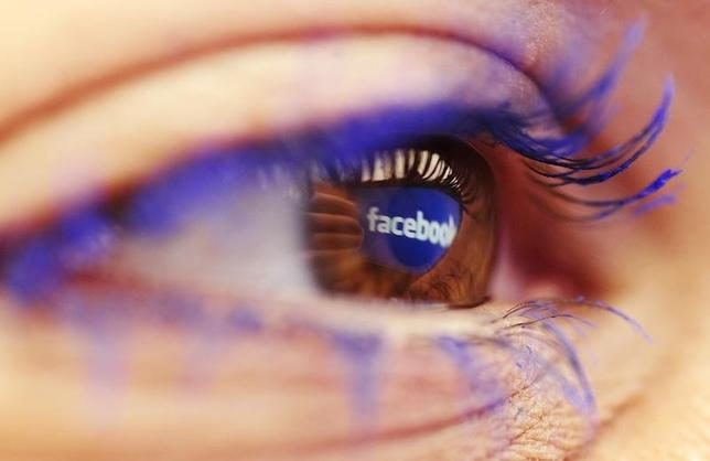 A Facebook logo reflected in the eye of a woman is seen in this picture illustration taken in Skopje November 6, 2014 REUTERS/Ognen Teofilovski