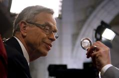 Finance Minister Joe Oliver looks at a reporters button after delivering the federal budget on Parliament Hill in Ottawa April 21, 2015. REUTERS/Patrick Doyle
