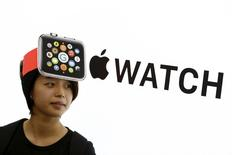 A woman wearing a mock-up of an Apple Watch stands in front of an Apple sign at an electronics store in Tokyo April 24, 2015. REUTERS/Thomas Peter