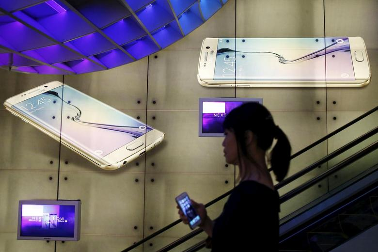 A woman holding an Apple iPhone passes a Samsung Galaxy S6 advertisement at a mall in Singapore April 24, 2015. REUTERS/Edgar Su