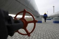 Сотрудник Газпрома на газовой станции в Судже под Курском 5 декабря 2008 года. Газпром ждет среднюю цену газа в 2015 году на уровне $242 за 1.000 кубометров при цене нефти $55 за баррель, сообщили член правления концерна Александр Медведев и финдиректор Андрей Круглов в ходе телеконференции. REUTERS/Denis Sinyakov