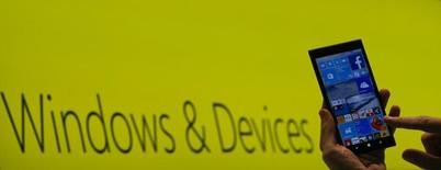 Сотрудник Microsoft держит смартфон с ОС Windows 10 на выставке CeBIT в Ганновере. 15 марта 2015 года. Microsoft Corp облегчит доступ приложений, разработанных для ОС Android и iOS ее конкурентов Google Inc и Apple Inc, к телефонам на базе ОС Windows в надежде привлечь интерес к своим непопулярным мобильным устройствам, сообщил директор компании по операционным системам. REUTERS/Morris Mac Matzen