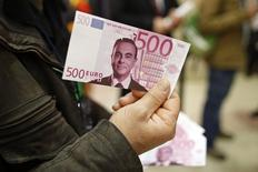 A labour council representative holds a facsimile 500 euros note with the portrait of Carlos Ghosn, Chairman and CEO of the Renault-Nissan Alliance, before the French carmaker Renault's shareholders general meeting in Paris, France, April 30, 2015. REUTERS/Benoit Tessier