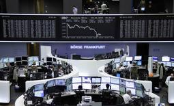 Traders are pictured at their desks in front of the DAX board at the Frankfurt stock exchange, Germany, April 29, 2015.     REUTERS/Remote/Staff
