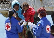 Mulher recebe ajuda para desembarcar de navio da Marinha da Itália em porto na Sicília. 04/05/2015 REUTERS/Antonio Parrinello
