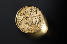 Монеты номиналом 1 австралийский доллар. Сидней, 27 июля 2011 года. Австралийский доллар растет после кратковременного спада, вызванного снижением процентных ставок Резервным банком Австралии. REUTERS/Tim Wimborne