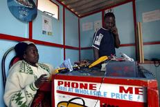 A customer (R) makes a call from a cellular phone shop in Harare, Zimbabwe June 20, 2006. Zimbabwe offers a sharp contrast to the rest of Africa, where mobile phone use is spreading rapidly as an alternative to unreliable and expensive fixed lines. But foreign currency shortages have hamstrung network expansion and growth in Zimbabwe's mobile phone sector, capping penetration at around 5 percent of the population, compared to 70 percent in South Africa or around 40 percent in Namibia. To match feature Telecoms-Zimbabwe. Picture taken June 20, 2006.  REUTERS/Stringer (Zimbabwe) - RTR1EVKN