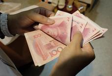 Una mujer cuenta billetes de yuan en un mercado de Pekín, el 1 de julio de 2013. China mantendrá una política monetaria ni muy ajustada ni muy expansiva para ayudar a apuntalar a su economía, que enfrenta vientos en contra y una perspectiva de inflación benigna, dijo el banco central el viernes en su informe trimestral de política monetaria. REUTERS/Jason Lee