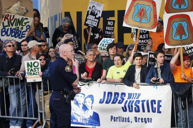 Protesters, many against the so-called fast track trade authority of the Trans-Pacific Partnership (TPP) trade agreement, rally outside the hotel where U.S. President Barack Obama is participating in a Democratic National Committee (DNC) event in Portland, Oregon May 7, 2015. REUTERS/Jonathan Ernst