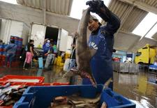 Una vendedor en una pescadería en Villa María del Triunfo, a las afueras de Lima, mar 30 2015. La economía peruana se habría acelerado en marzo frente a meses previos debido a una recuperación del vital sector primario, que habría sido opacado por el retroceso de la actividad de la construcción, según un sondeo de Reuters difundido el miércoles. REUTERS/Mariana Bazo