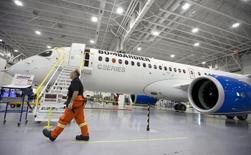 Un trabajador de Bombardier camina junto al avión CS300 en el hangar, antes de su prueba de vuelo, en Mirabel, Quebec, 27 de febrero de 2015. El fabricante canadiense de trenes y aeronaves Bombardier Inc dijo el jueves que planea recortar 1.750 puestos de trabajo en su división de aviones ejecutivos, principalmente debido a la debilidad de la demanda de sus aeronaves Global. REUTERS/Christinne Muschi