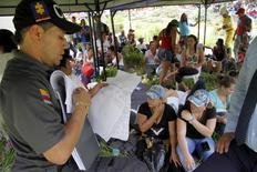 Un policía lee un documento mientras los parientes de los mineros atrapados esperan por noticias, en Riosucio, provincia de Caldas, Colombia, 14 de mayo de 2015. Los organismos de socorro rescataron los primeros cuatro cadáveres de los 15 trabajadores que murieron ahogados en una mina subterránea de oro que se inundó en una región montañosa del noroeste de Colombia, informó el viernes el Gobierno. REUTERS/Stringer
