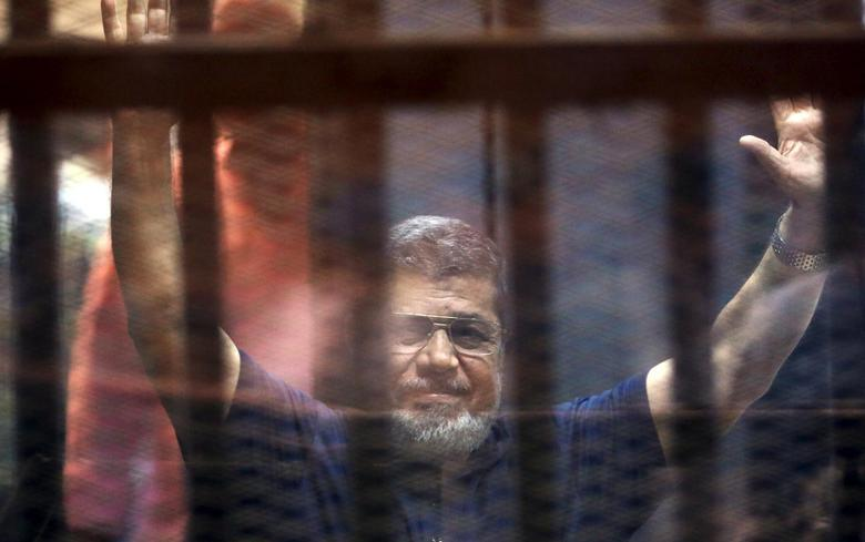 Former Egyptian President Mohamed Mursi waves as he enters for his trial with other Muslim Brotherhood members at a court in the outskirts of Cairo, May 16, 2015.  REUTERS/Mohamed Abd El Ghany