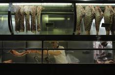 Un carnicero ordena carne luego de cortarla, dentro de un puesto en el Mercado Municipal en Sao Paulo, 10 de octubre de 2014. El Ministerio de Agricultura de Brasil dijo el martes que China terminó un embargo sobre importaciones de carne bovina brasileña que estaba vigente desde 2012. REUTERS/Nacho Doce