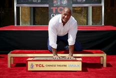 "Actor Dwayne ""The Rock"" Johnson poses with his hands in cement during his hand and footprints ceremony in the forecourt of the TCL Chinese Theatre in celebration of his new movie ""San Andreas,"" in Hollywood, California May 19, 2015. REUTERS/Danny Moloshok"