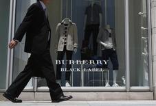 Прохожий у магазина Burberry в Токио. 12 мая 2014 года. Британский ритейлер одежды и аксессуаров премиум-класса Burberry понизил прогноз прибыли от оптовых и розничных продаж в 2016 году из-за динамики валютных курсов и заявил об ожидаемом росте волатильности на ряде рынков, испортив впечатление от превысивших прогнозы результатов. REUTERS/Yuya Shino