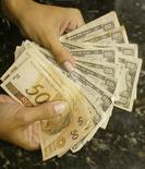 Caixa troca reais por dólares em casa de câmbio no Rio de Janeiro. 07/05/2004. REUTERS/Bruno Domingos