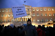 """Un hombre en una protesta pro-gobierno sostiene un cartel que dice """"Todo lo que estamos diciendo es denle una oportunidad a Grecia"""", afuera del parlamento en Atenas, 11 de febrero de 2015. Grecia no será capaz de afrontar un pago al Fondo Monetario Internacional que vence el 5 de junio si los prestamistas foráneos no le dan más ayuda, dijo el miércoles un alto cargo del Gobierno heleno, en la última advertencia de Atenas de que está al borde de un default. REUTERS/Yannis Behrakis"""