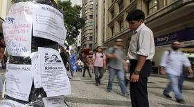 Una persona revisa unos anuncios de empleo colocados en un poste en Sao Paulo, mar 19 2015. La actividad económica en Brasil se desplomó en el primer trimestre y el desempleo subió a un máximo de casi cuatro años, lo que se sumó a señales de una dolorosa recesión que podría empeorar pese a que el Gobierno reduce el gasto.  REUTERS/Paulo Whitaker