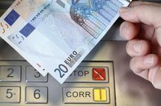 """Женщина держит купюры 20 и 50 евро у банкомата в Берне. 16 января 2015 года. Украина рассчитывает получить во второй половине июня первый транш на сумму 600 миллионов евро из новой макрофинансовой помощи ЕС общим объемом 1,8 миллиарда евро, соглашение о предоставлении которой было подписано в Риге в рамках саммита """"Восточного партнерства"""". REUTERS/Thomas Hodel"""