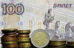 """Монеты валюты евро на фоне рублевой купюры в Зенице 21 апреля 2015 года. Торги долларом расчетами """"сегодня"""" на Московской бирже не проводятся, а расчетами """"завтра"""" валюта США к 10.15 МСК была вблизи отметки 49,87 рубля, на треть процента ниже предыдущего биржевого закрытия.  REUTERS/Dado Ruvic"""
