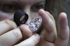 Женщина изучает алмаз в офисе компании, принадлежащей Алросе, в Москве 17 октября 2013 года. Крупнейший в мире алмазодобытчик Алроса в понедельник объявила о второй в этом году находке крупного алмаза в Якутии, предварительно оценив камень примерно в 45 раз выше средней цены своих ювелирных камней. REUTERS/Sergei Karpukhin