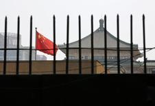 La bandera de China ondea detrás de una reja en la sede de la La Comisión Nacional de Desarrollo y Reforma (NDRC), en Beijing, 12 de julio de 2013. La agencia de planificación estatal de China publicó el lunes una lista de más de 1.000 proyectos propuestos cuyo valor total ascendería a 1,97 billones de yuanes (317.750 millones de dólares) que invita a que los inversores privados ayuden a financiar, construir y operar. REUTERS/Kim Kyung-Hoon