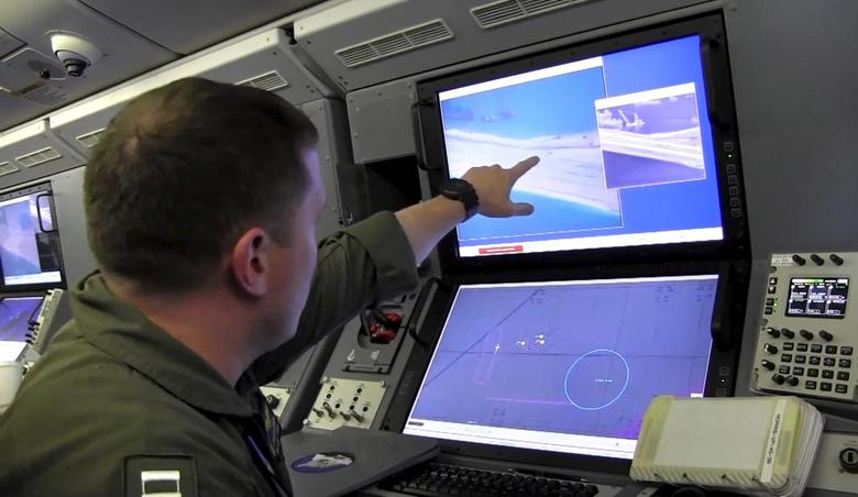 A U.S. Navy crewman aboard a P-8A Poseidon surveillance aircraft views a computer screen purportedly showing Chinese construction on the reclaimed land of Fiery Cross Reef in the disputed Spratly Islands in the South China Sea in this still image from video provided by the United States Navy May 21, 2015. REUTERS/U.S. Navy/Handout via Reuters