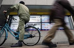 Un hombre en bicicleta mira a un tablero electrónico que muestra el índice Nikkei de la Bolsa de Tokyo, 24 de febrero de 2015. Las bolsas de Asia subían el martes, revirtiendo unas pérdidas tempranas gracias a las ganancias en Hong Kong y China continental, y el dólar extendía los avances de la sesión anterior, anotando un máximo en ocho años frente al yen. REUTERS/Yuya Shino
