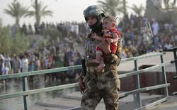 Soldado iraquiano leva menino de Ramadi desabrigado nos arredores de Bagdá. 19/05/2015 REUTERS/Stringer
