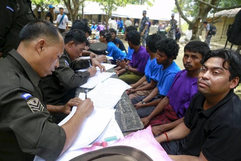 Rohingya Muslims from Myanmar, who were rescued by the Myanmar navy alongside Bangladesh refugees, are interviewed by immigration officers at a Muslim religious school used as a temporary refugee camp, at the Aletankyaw village in the Maungdaw township, in Rakhine state May 23, 2015. REUTERS/Soe Zeya Tun