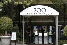 A man carries flowers into the Sunset Marquis hotel where U2 tour manager Dennis Sheehan was pronounced dead in his hotel room, according to local media, in West Hollywood, California May 27, 2015.  REUTERS/Patrick T. Fallon