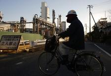 A worker cycles past a petro-industrial complex in Kawasaki near Tokyo December 18, 2014. REUTERS/Thomas Peter