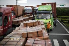 Camiones que transportan cobre y otros bienes, esperan para entrar a la zona de comercio libre, en Shanghái, 24 de septiembre de 2014. El crecimiento de la demanda de cobre por parte de China se vería afectado en el 2016 por una nueva directriz de los reguladores que podría llevar a reemplazarlo por metales más baratos como el aluminio para la fabricación de cables, dijo el lunes Goldman Sachs. REUTERS/Carlos Barria