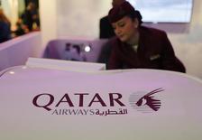 Una asistente de vuelo de la aerolínea Qatar Airways, muestra el nuevo asiento clase business de la compañía durante una exhibición en Dubai, 6 de mayo de 2013. Qatar Airways planea convertirse en patrocinador del Mundial de la FIFA aunque esté preocupado por la investigación de sobornos del órgano que rige el fútbol mundial, dijo la aerolínea el martes. REUTERS/Ahmed Jadallah