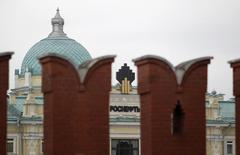 Логотип Роснефти на фоне зубцов стены московского Кремля 27 мая 2013 года.  Крупнейшая российская нефтекомпания Роснефть формирует свой бизнес-план без учета возможного получения средств из Фонда национального благосостояния (ФНБ), сообщил Рейтер представитель компании. REUTERS/Sergei Karpukhin