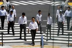 Trabajadores de oficina reflejados en un vidrio mientras cruzan la calle durante la hora de almuerzo, en Tokyo, 1 de junio de 2015. La Organización para la Cooperación y el Desarrollo Económico (OCDE) recortó su previsión del crecimiento económico mundial para este año, pero dijo que espera que los precios más bajos del petróleo aseguren una recuperación gradual, aunque la inversión débil sigue siendo una preocupación. REUTERS/Thomas Peter