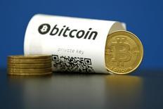 Unas monedas de Bitcoin junto a un papel moneda de la misma divisa con un código QR en La Maison du Bitcoin en París, mayo 27 2015. El estado de Nueva York emitió el miércoles las reglas finales para las empresas que operan con dinero virtual como bitcoin, con muy pocas modificaciones para aplacar las quejas de que una regulación muy dura podría perjudicar a un mercado en ciernes.  REUTERS/Benoit Tessier