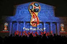 Журналисты смотрят на логотип чемпионата мира по футболу 2018 года, проекция которого выведена на здание Большого театрав Москве 28 октября 2014 года. Расследование ФБР взяточничества в ФИФА включает изучение обстоятельств того, как международное футбольное ведомство наделяло правами принять чемпионаты мира Россию и Катара. REUTERS/Maxim Shemetov