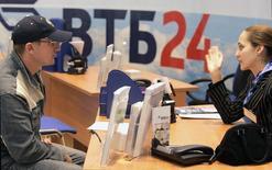 Сотрудник банка ВТБ общается с клиентом. Москва, 27 апреля 2007 года. Банк России считает, что для приобретения физическими лицами ОФЗ не существует никаких ограничений, но стимулирование государством перетока средств населения с депозитов в ОФЗ может потребовать от властей больше господдержки для банков. REUTERS/Alexander Natruskin