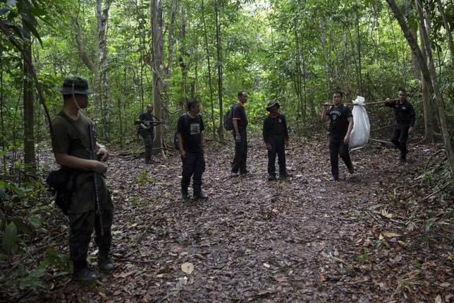 Members of a police forensic team carry a body bag with human remains dug from the grave near the abandoned human trafficking camp in the jungle close the Thailand border at Bukit Wang Burma in northern Malaysia May 27, 2015. REUTERS/Damir Sagolj