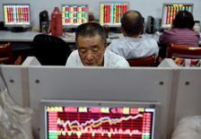 Брокерская контора в Ханчжоу. 22 мая 2015 года. Азиатские фондовые рынки, кроме Китая, снизились в пятницу и за неделю из-за озабоченности инвесторов финансовым положением Греции и накануне публикации отчета о занятости в США. REUTERS/China Daily