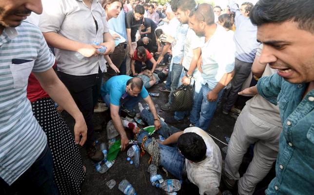 Injured people get first aid after an explosion during an election rally of pro-Kurdish Peoples' Democratic Party (HDP) in Diyarbakir, Turkey, June 5, 2015. An explosion apparently caused by an electrical fault injured several people at an opposition party rally in Turkey's mainly Kurdish city of Diyarbakir on Friday, days before parliamentary elections. Television footage showed people being carried out on stretchers as organisers of the rally for the pro-Kurdish Peoples' Democratic Party (HDP) announced on loudspeakers that the explosion had been caused by a fault in a power generator and urged people to stay calm. REUTERS/Stringer      TPX IMAGES OF THE DAY