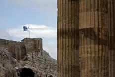 Varias personas junto a una bandera griega en la Acrópolis de Atenas, en Grecia, el 7 de junio de 2015. La Comisión Europea recibió el martes nuevas propuestas de Grecia mientras negocia un nuevo acuerdo de deuda con sus acreedores internacionales, dijo un portavoz del ejecutivo europeo en una conferencia de prensa. REUTERS/Alkis Konstantinidis