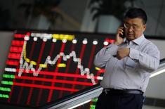 Un hombre habla por celular dentro del edificio de la Bolsa de Shanghái, en el distrito financiero de Pudong, en Shanghái, 17 de noviemebre de 2014. Las bolsas de Asia se hundían el martes luego de que la especulación de un alza en las tasas de interés en Estados Unidos tan pronto como en septiembre golpeó a los mercados emergentes, pero no logró dar un impulso duradero al dólar. REUTERS/Carlos Barria