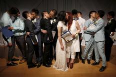 Couples kiss after getting married at a group wedding for seven same-sex couples from China, in West Hollywood, California, United States, June 9, 2015. REUTERS/Lucy Nicholson