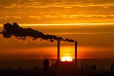 """Солнце всходит на фоне труб электростанции в Берлине 27 ноября 2013 года. Всемирный банк снизил прогноз роста мировой экономики в 2015 году, призвав страны """"пристегнуть ремни"""" на период привыкания к низким ценам на сырье и возможному скорому повышению процентных ставок американской Федеральной резервной системой (ФРС). REUTERS/Thomas Peter"""
