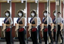 Женщина-турист с маской на лице отражается в зеркале в Сеуле 8 июня 2015 года. Центробанк Южной Кореи снизил в четверг процентные ставки до рекордного минимума: власти спешат минимизировать урон, нанесенный распространением коронавируса MERS. REUTERS/Kim Hong-Ji